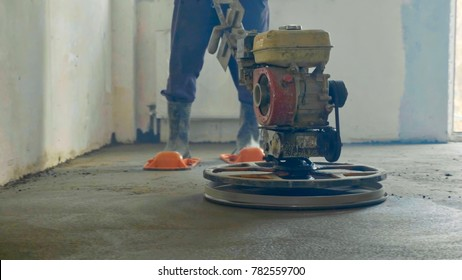 Builder polishing mortar floor at construction site of new appartments. Mechanized grout screed concrete floor close-up
