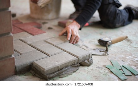 builder puts tiles in the yard. Paving slab. DIY home improvement.