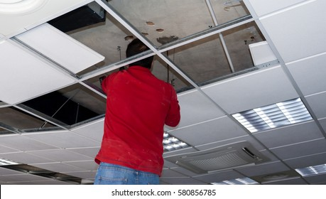 Builder putting or repairing up a suspended ceiling