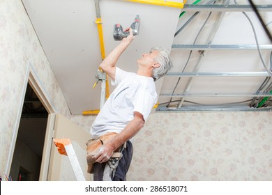 Builder putting up a suspended ceiling