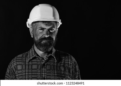 Builder or repairer with thick beard. Construction and hard work concept. Man with confident face isolated on black background, copy space. Worker with brutal image wears white helmet and plaid shirt.