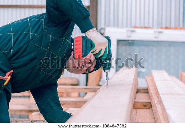 The builder with a screwdriver A man screws a screwdriver with an electric screwdriver into a wooden board