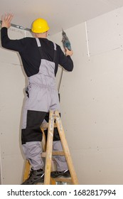 A builder standing on a ladder installs drywall at a construction site