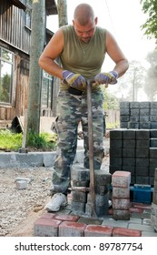 builder straightens bricks using crowbar in a newly-paved street.