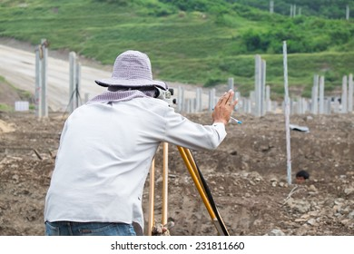 Builder surveyor working with optical equipment level at construction site.