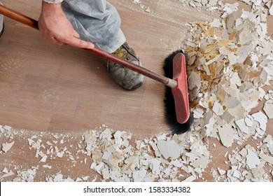 Bauer, der nach der Renovierung den Boden fegt