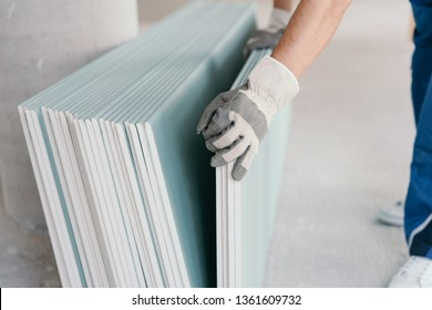 Builder taking a sheet of chip board cladding from a stack against the wall with his gloved hands indoors in a new build home