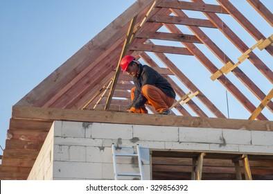 Builder trying to board attic floor joists