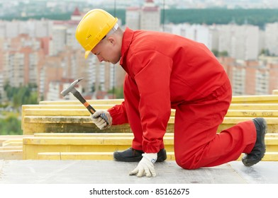 builder in uniform working with hammer and nail at construction site