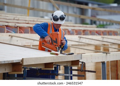 A builder uses a nail gun to secure timber on the verandah of new building