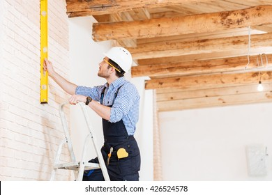Builder using consruction level and standing n the ladder at the working area
