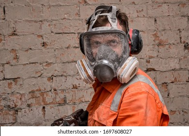 Builder wearing full face respirator mask and ear defenders for working in dusty and noisy environment.