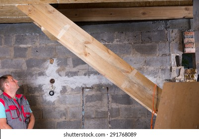 Builder Wearing Vest Standing in Unfinished Basement Inspecting Work on Wooden Staircase Inside New Home Construction Site
