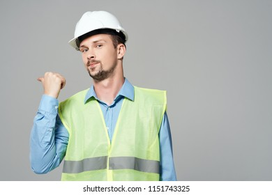 builder in a white helmet and in a yellow waistcoat on a gray background