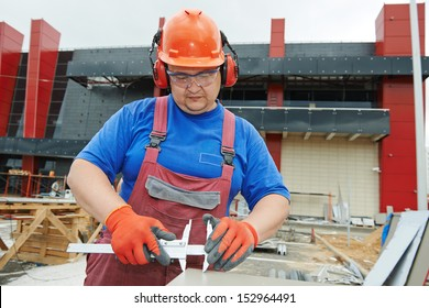 Builder worker with caliper measure plastic parts at construction site