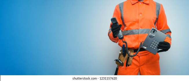 Builder worker is holding in hand a handset phone isolated on blue background with copy space. Call to a repair man concept. Contact us.