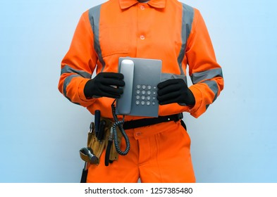 Builder worker is holding in hand a handset phone. Call a repairman concept. Contact us.
