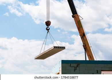 Builder worker installing concrete floor slab panel at building construction site. Second floor house concrete floor slab installation