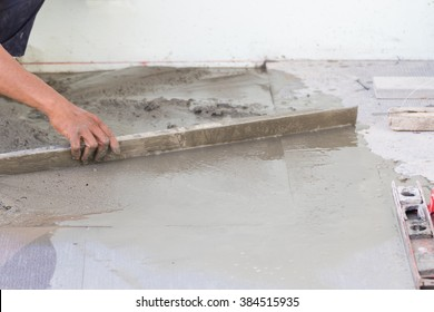 Builder worker plastering concrete at floor of house construction