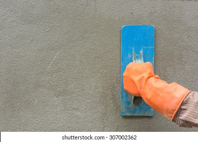 Builder worker plastering concrete at wall