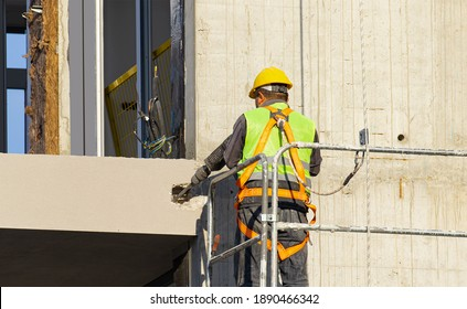 Builder worker with pneumatic hammer drill equipment making hole in concrete wall at construction site
