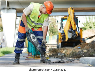 Builder worker with pneumatic hammer drill equipment breaking asphalt at road construction site