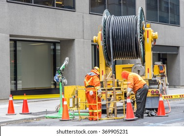 Builder worker with pneumatic hammer drill equipment breaking asphalt at road construction site - Two workers draining sewer on the streets