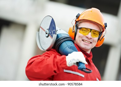 builder worker in safety protective equipment with grinding machine power tool at construction site