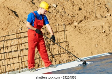 builder worker in uniformcovering roof with insulation tar material at construction site