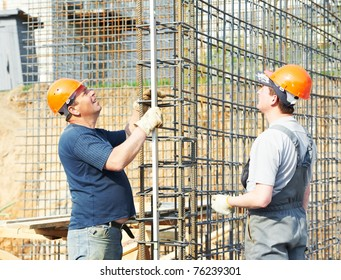 builder workers checking metal rods bars in framework reinforcement for concrete pouring by level at construction site