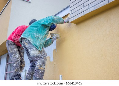 builder workers plastering exterior wall, facade plasterers at work.