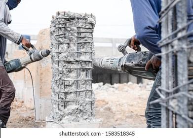 Builder workers using pneumatic hammer drill equipment breaking concrete bridge pillars at road construction site.