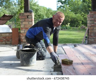 The builder in working clothes is doing construction works - Terrace tiling