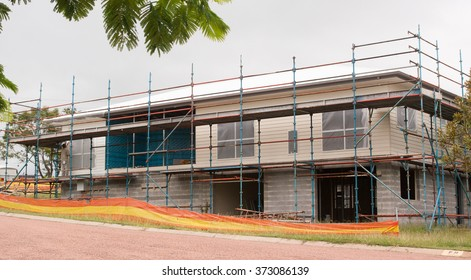 Builder working on house construction using scaffold