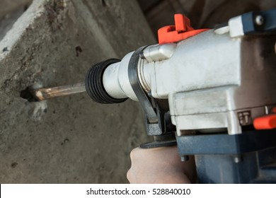 builder working perforator, punch the wall cuts, perforating gun in the hands of men, construction tools, a broken wall.