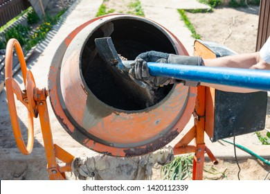 builder working with shovel during concrete cement solution mortar preparation. construction worker with a bucket in his hands loads a concrete mixer.orange concrete mixer prepares cement mortar