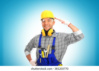 Builder in yellow helmet, protective glasses and working clothes