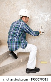 Builder-repairman plasterer in a protective helmet while repairing applies decorative plaster, pattern on the wall, sitting - Shutterstock ID 1953679315