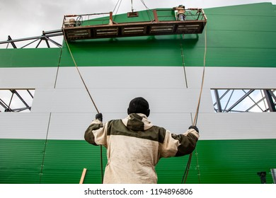 The builders are building a building of metal structures at a height in the construction cradle, in the foreground is a builder holding ropes against a blue sky. Violation of safety at a construction