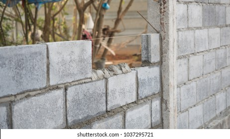 Builders are building walls with brick and mortar.