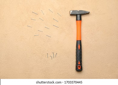 Builder's hammer with nails on color background