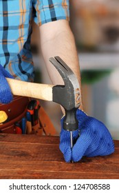 Builder's hands hammering nail into wood