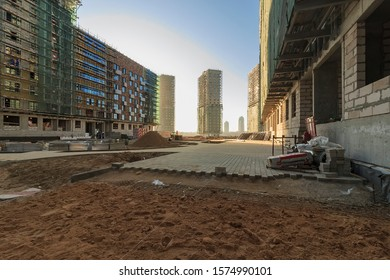 Builders laid tile on sidewalk in courtyard of residential building under construction. poorly laid pavement tiles on walkway in town park. stone paving blocks laid on pallets, preparing. Moscow 2019.