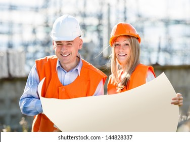 builders are laughing holding a white sheet of