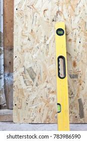Builders level near the fiberboard wall