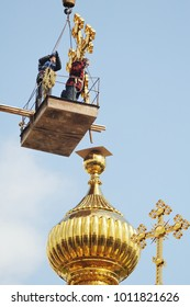 builders lifted on a crane large gold cross to be installed on the dome of the Orthodox church.