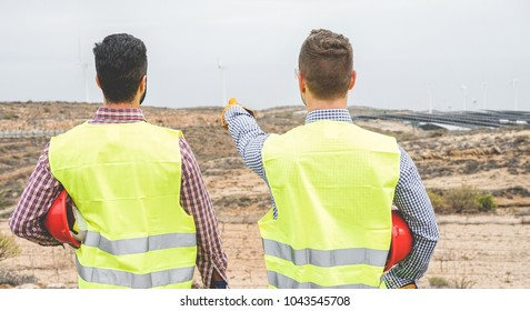Builders pointing new area for building  wind farm and photovoltaic plant site - Happy workers planning new projects - Dealing, real estate, engineer, industrial concept - Focus on right man head