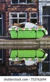 Builders skip and its reflection near a canal in Gouda in the Netherlands