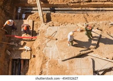 Builders slingers repairing sewers .Working with crane
