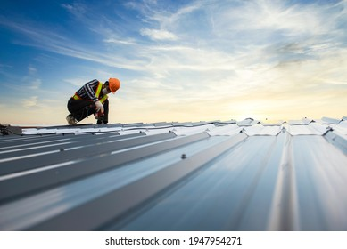 Builders in work clothes install new roofing tools, roofing tools, electric drill and use them on new wooden roofs with metal sheets